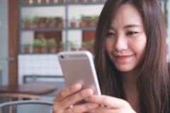 一名美丽的亚裔妇女的特写镜头图象有兴高采烈的面孔藏品和使用的巧妙的电话,当喝在木桌上时的热的咖啡 免版税图库摄影
