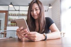 一名美丽的亚裔妇女的特写镜头图象有兴高采烈的面孔藏品和使用的巧妙的电话 免版税库存图片