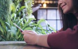 一名美丽的亚裔妇女的特写镜头图象递拿着和使用巧妙的电话在现代咖啡馆 免版税图库摄影