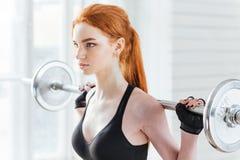 一名美丽的健身妇女的特写镜头画象有杠铃的 库存图片