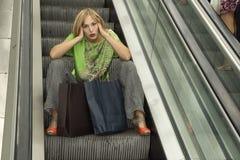 一名美丽的典雅的年轻白肤金发的妇女的画象购物中心自动扶梯的与袋子 库存照片