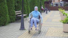 一名美丽的回教妇女的画象hijab的残疾在街道上的一个轮椅 股票视频