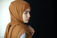一名美丽的回教妇女的画象报道她的头的一条绿色围巾的 图库摄影