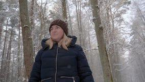 一名美丽的女孩妇女通过森林走,看  免版税库存图片