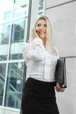一名美丽的女实业家谈话在电话在窗口旁边 免版税库存照片