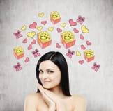一名美丽的妇女作梦关于礼物 礼物和心脏象在混凝土墙上得出 免版税库存照片