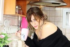 一名美丽的妇女在厨房里喝咖啡 库存照片