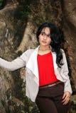 一名美丽的妇女在大树下 免版税库存照片