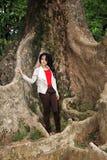 一名美丽的妇女在大树下 图库摄影