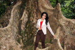 一名美丽的妇女在大树下 免版税图库摄影