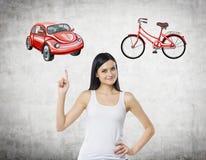 一名美丽的妇女尝试选择了旅行或通勤的最适当的方式 她的选择是汽车 汽车的两个剪影 免版税库存图片