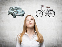一名美丽的妇女尝试选择了旅行或通勤的最适当的方式 汽车和自行车的两个剪影是博士 免版税图库摄影
