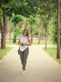 一名美丽的妇女的步行一件白色衬衣的在公园 免版税库存照片