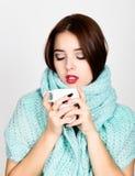 一名美丽的妇女的特写镜头画象羊毛围巾、饮用的热的茶或者咖啡的从白色杯子 库存照片