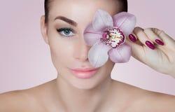 一名美丽的妇女的画象一个温泉沙龙的与一朵兰花在她的手上 免版税库存图片
