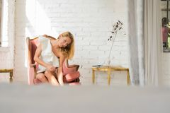 一名美丽的妇女的画象一把古色古香的扶手椅子的 库存图片