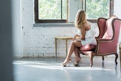 一名美丽的妇女的画象一把古色古香的扶手椅子的 免版税图库摄影