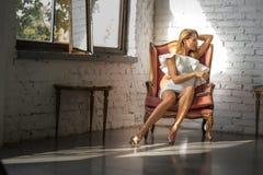 一名美丽的妇女的画象一把古色古香的扶手椅子的 库存照片