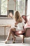 一名美丽的妇女的画象一把古色古香的扶手椅子的 免版税库存图片