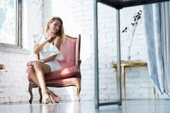 一名美丽的妇女的画象一把古色古香的扶手椅子的 图库摄影