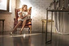 一名美丽的妇女的画象一把古色古香的扶手椅子的 免版税库存照片