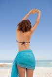 一名美丽的妇女的背面图提高她的胳膊机智的海滩装的 库存照片