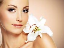 一名美丽的妇女的面孔有干净的皮肤和白花的 库存照片