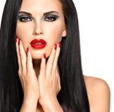 一名美丽的妇女的面孔有红色钉子和嘴唇的 免版税库存照片
