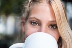 一名美丽的妇女的顶头射击注视喝一杯咖啡 图库摄影