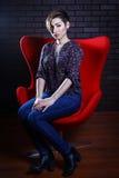 一名美丽的妇女的画象一把红色扶手椅子的 免版税库存照片