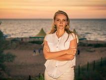 一名美丽的妇女的画象一件白色无袖的衬衣的在日落海的背景 免版税库存图片
