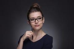 一名美丽的妇女的画象企业样式的 在灰色bac 免版税库存图片
