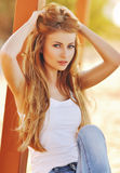 一名美丽的妇女的画象有壮观的头发的在一件白色上面和时髦的牛仔裤 库存图片