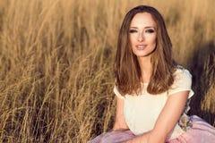 一名美丽的妇女的画象有长的头发佩带的白色丝绸上面的和桃红色遮掩避开坐在黄色领域 库存图片