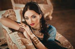 一名美丽的妇女的画象用印地安繁体中文的穿戴,当她的手绘与无刺指甲花mehendi 女孩坐lu 免版税库存图片