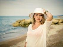 一名美丽的妇女的画象石头背景的在海滩的 免版税库存图片
