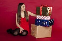 一名美丽的妇女看很大数量的礼物 库存照片