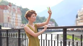 一名美丽的妇女采取在一个智能手机的一selfie在城市的背景 旅行,游人,夏天 影视素材