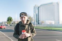 一名美丽的年轻学生的画象有一杯咖啡的在城市背景的手上 有一份饮料的微笑的年轻人在 库存照片