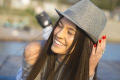 一名美丽的年轻微笑的妇女的画象有帽子的,当说谎时 免版税库存图片