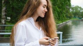 一名美丽的年轻成功的妇女的画象有电话的 有长的头发的欧洲女孩使用一个智能手机并且打印a 股票录像