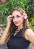 一名美丽的年轻深色的妇女的画象有一朵花的在她的耳朵后,在一个开花的庭院里 美好的微笑 免版税库存图片