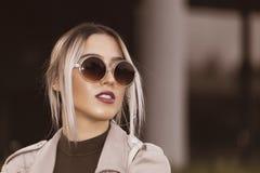 一名美丽的年轻现代妇女的画象有太阳镜的 免版税库存照片