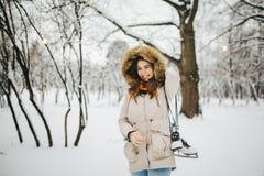 一名美丽的年轻白种人妇女在一件夹克的一个多雪的公园站立有一张敞篷和毛皮的在她的头在牛仔裤并且举行一个对  免版税库存图片