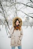 一名美丽的年轻白种人妇女在一件夹克的一个多雪的公园站立有一张敞篷和毛皮的在她的头在牛仔裤并且举行一个对  免版税库存照片