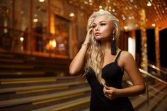 一名美丽的年轻白肤金发的妇女的画象夜城市的背景的 免版税库存图片
