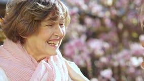 一名美丽的年长妇女的春天画象谈话与她的成人女儿 母亲节,家庭天 退休的愉快 影视素材