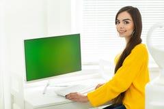 一名美丽的微笑的妇女的画象,运作在有绿色屏幕的计算机,在办公室环境里 免版税库存照片