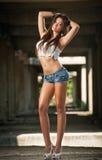 一名美丽的性感的妇女的画象有牛仔布短裤和白色的在都市背景中播种了T恤杉 有吸引力浅黑肤色的男人摆在 免版税库存图片