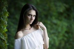 一名美丽的愉快的微笑的白种人妇女的画象白色礼服的有开放肩膀、干净的皮肤、长的头发和偶然构成的 库存照片